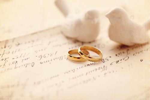 beschriebenes Papier mit goldenen Ringen und weißen Vögeln
