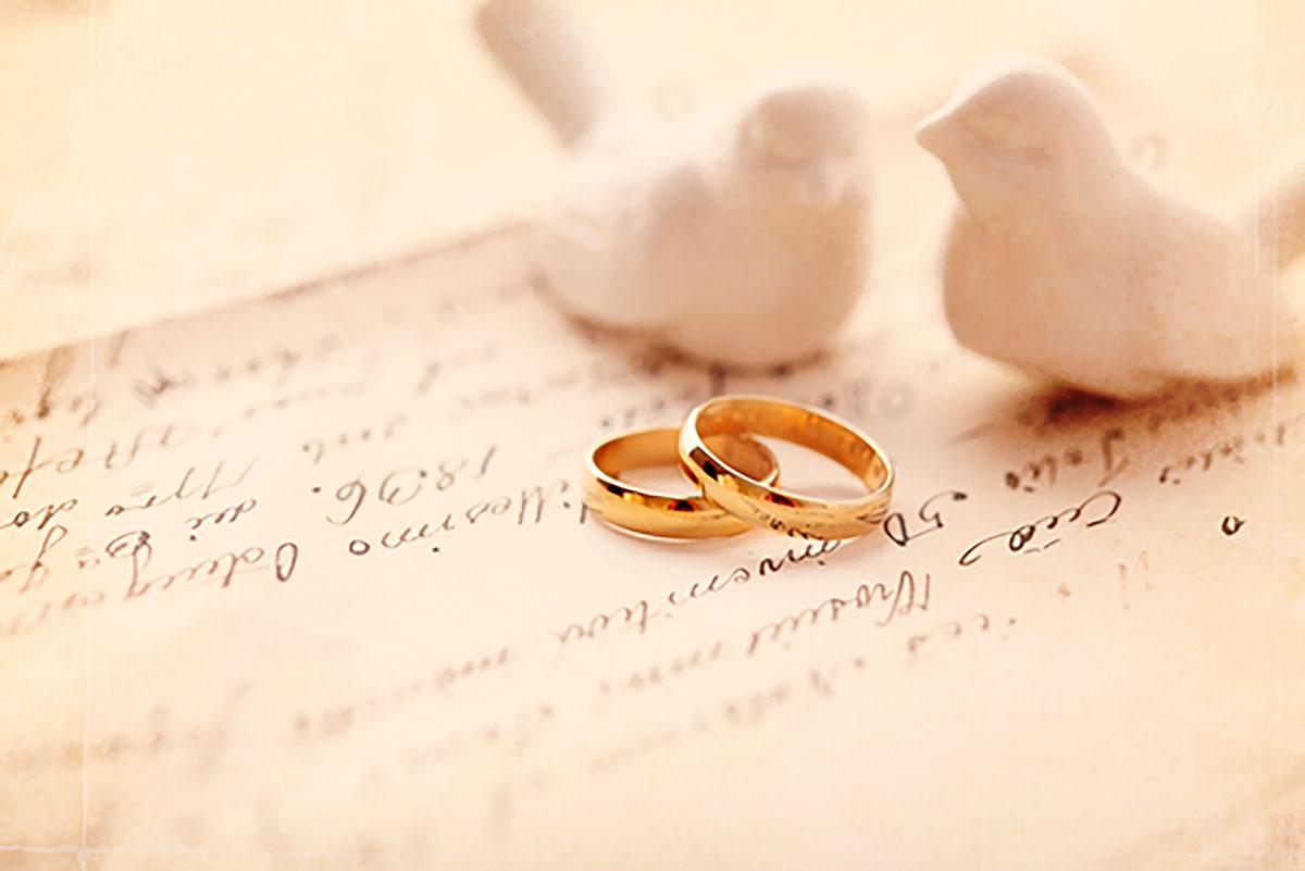 Goldene Ringe mit weißen Vögeln auf beschriebenen Papier