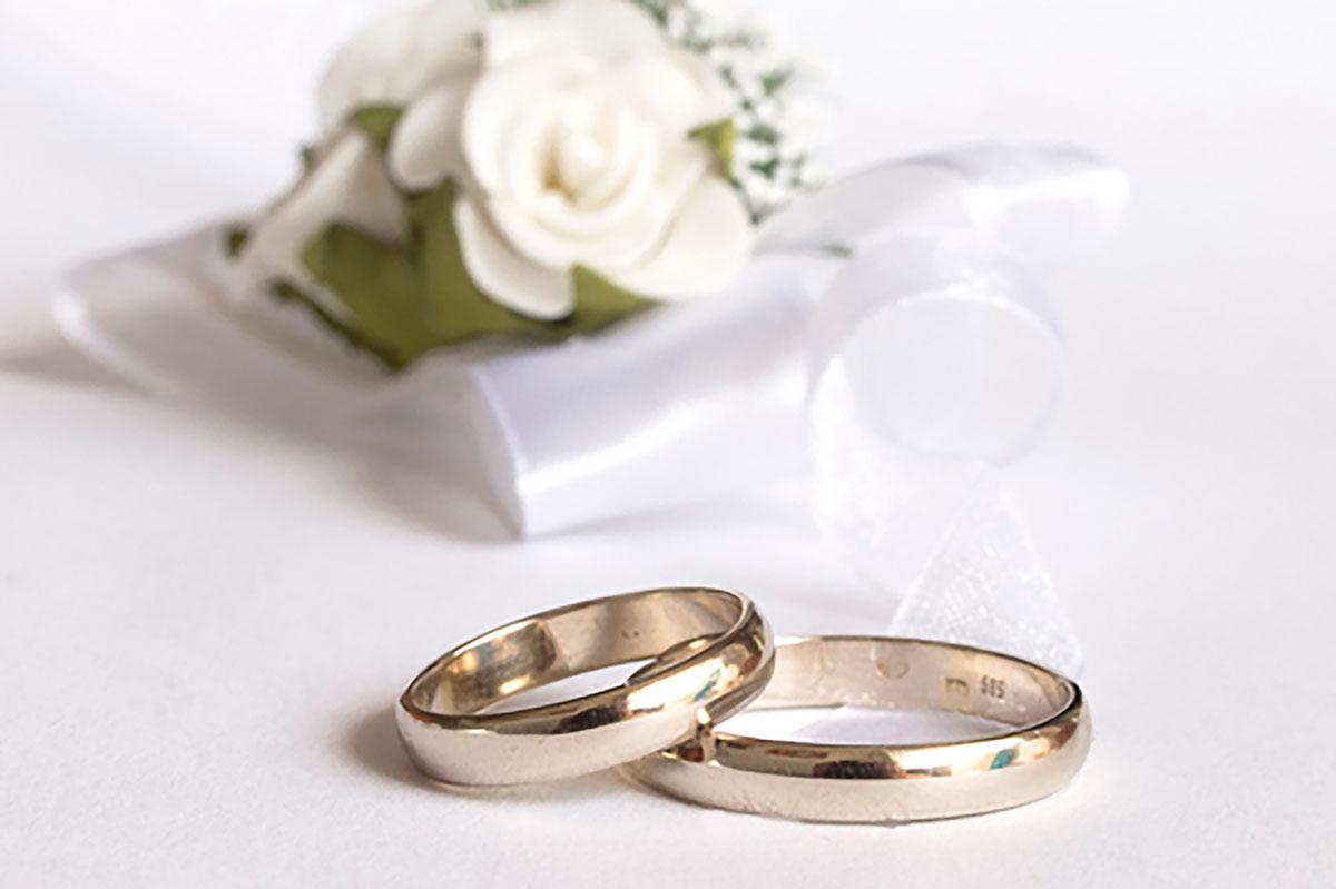 Ringe auf weißem Papier mit weißen Rosen zur Eisernen Hochzeit